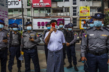 A plain clothes policeman takes a smart phone photograph of the journalists and protestors as a huge crowd gathered in the city centre to protest the 1 February 2021 military coup and to show their su...