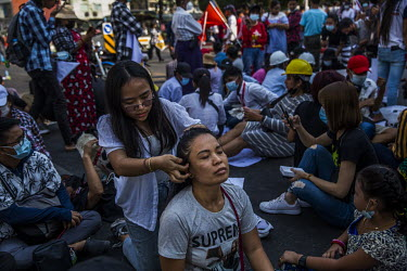 Protestors style their hair as they block a road at Myaynigone junction as they demonstrate against the military coup.