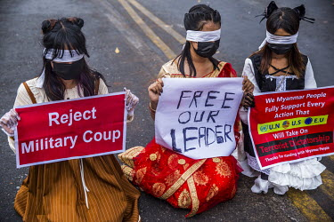 Three woman wearing traditional costumes and blindfolded sit in front of a police barricade blocking off the Sule Square from protestors against the 1 February 2021 military coup and in support of the...