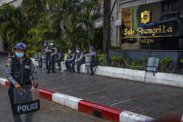 Police rest in front of the Shangri-La hotel which is currently closed.