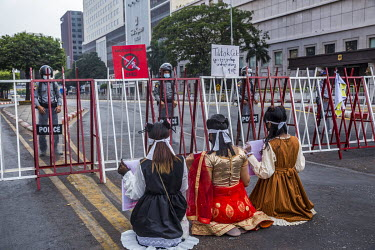 Three woman wearing traditional costumes sit in front of a police barricade blocking off the Sule Square from protestors against the 1 February 2021 military coup and in support of the Civil Disobedie...
