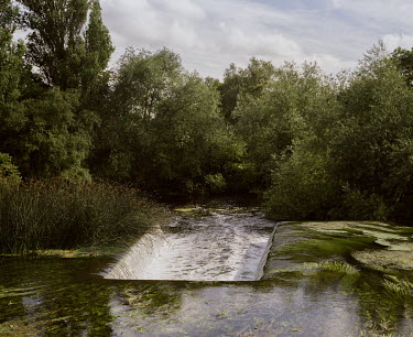 Water flows, via a weir, from the Grand Union Canal into the River Colne in Harefield.