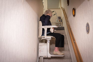A 90 year-old woman uses a stair lift as she heads out to visit a vaccination centre for her second Pfizer-BioNTech vaccination to protect her against COVID-19.