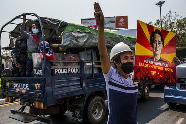 A protestor makes the three finger salute next to a police truck.