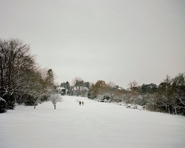 People walk across a snow covered fairway at Banstead Downs Golf Club south of London.