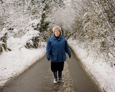 A woman out walking in snowy conditions on Rydons Lane, Colusdon.