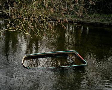 A abandoned partly submerged dinghy in the River Crane, Hanworth.