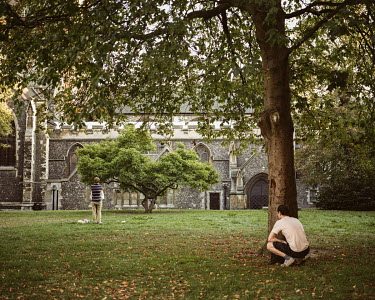A man watches a couple embrace in the garden of the All Saints Church in Kingston upon Thames.