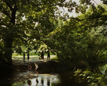 Children play in the River Roding, Roding Valley.