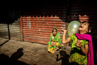 An elderly ywoman watches a girl playing laughing while playing with a balloon in the urban refugee camp popularly known as 'Geneva Camp'. The people living in the area are related to Muslims who move...