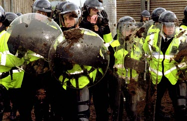 Mud splattered police face demonstrators at Hill Grove Cat Farm where 800 people took part in an anti-vivisection protest at the laboratory cat breeding farm.