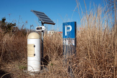 A solar powered radioactivity monitoring station installed in an abandoned car park.  The entire population of Futaba was evacuated en masse after the Fukushima Daiichi nuclear disaster. Since 2013, o...