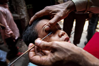 A man applies Kohl (surma) around a child's eyes before Friday prayers in the urban refugee camp popularly known as 'Geneva Camp'. The people living in the area are related to Muslims who moved here m...