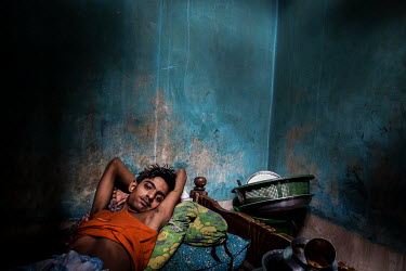 A youth rests on a bed in the urban refugee camp popularly known as 'Geneva Camp'. The people living in the area are related to Muslims who moved here mostly, but not exclusively, from Bihar in India...