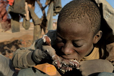 A boy eating rice at the Tabelote gold mine.