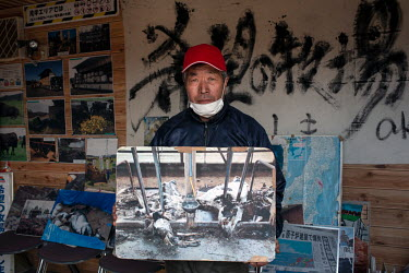 Farmer Masami Yoshizawa with a picture his cattle that died following the 2011 Fukushima Daiichi nuclear disaster.  The authorities ordered Mr Yoshizawa to slaughter the cows that survived and leave h...