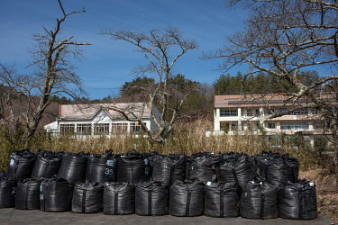 Plastic bags containing contaminated waste stacked in front of the abandoned Tsushima primary school.  The town of Namie, located about 9 km north of the nuclear plant, was evacuated as a result of th...