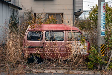 An abandoned vehicle and private home empty since March 2011 because of elevated radiation levels.  The entire population of Futaba was evacuated en masse after the Fukushima Daiichi nuclear disaster....