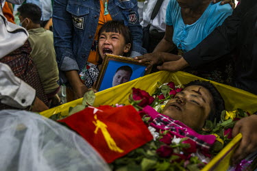 Shwe Yote Hlwar, the five year old daughter of Zwe Htet Soe (26), is held by her mother, Thet Htar, as she weeps while standing by the body of her father, a construction worker who was shot and killed...