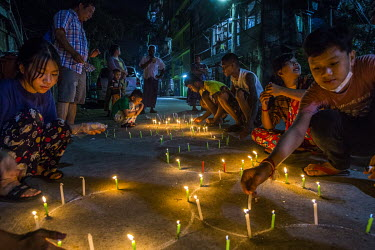 Children light candles as a memorial to those killed by the military and police during anti-coup protests.