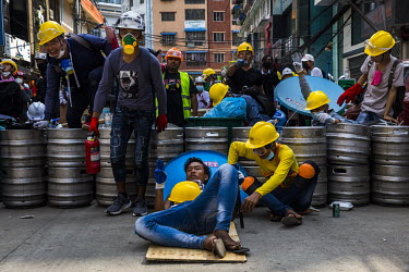 Protestors, wearing hard hats, goggles and face masks to protect themselves from the tear gas being used against them by the security forces, gather behind a barrier made from beer kegs during anti-co...