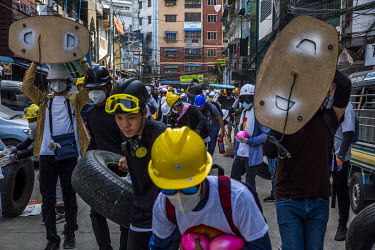Protestors, wearing hard hats, goggles and face masks to protect themselves from the tear gas being used against them by the security forces, use tyres and street furniture to form a makeshift barrier...