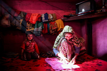 A woman and a boy together in a room, where the woman is sewing fabric, in the urban refugee camp popularly known as 'Geneva Camp'. The people living in the area are related to Muslims who moved here...