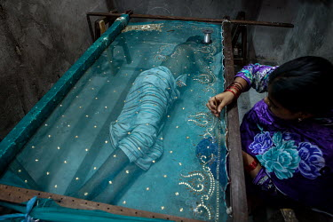 A woman doing piece work attaches beads and sequins to a fabric while a man sleeps beneath the work frame in the urban refugee camp popularly known as 'Geneva Camp'. The people living in the area are...