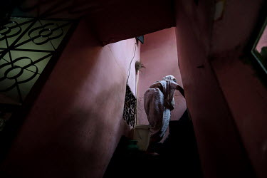 An elderly woman climbs a flight of stairs in a building in the urban refugee camp popularly known as 'Geneva Camp'. The people living in the area are related to Muslims who moved here mostly, but not...