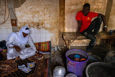 A gold trader who buys gold from the various artisanal gold mines that operate in the Sahara Desert in the north of the country, prepares to melt it into ingots which will be sold in Dubai and India.