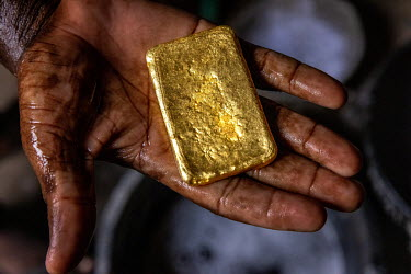 A gold trader who buys gold from the various artisanal gold mines that operate in the Sahara Desert in the north of the country, holds an ingot which will be sold in Dubai or India.