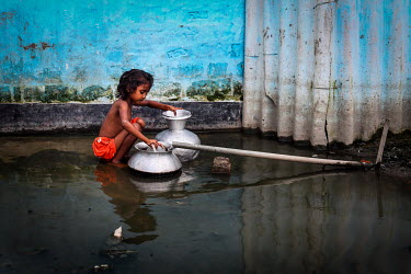 A girl collecting water in the urban refugee camp popularly known as 'Geneva Camp'. The people living in the area are related to Muslims who moved here mostly, but not exclusively, from Bihar in India...