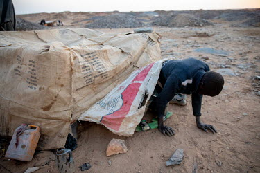 A miner leaves a makeshift shelter at an artisanal gold mine.