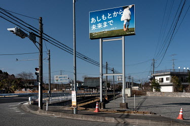 An advertising board for a construction company aiming to build the foundations for the future new town. The catch phrase reads: 'From the first steps to the future'.   The entire population of Futaba...