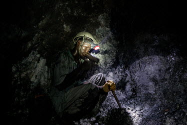 Young Fulani miner digging for gold ore at the bottom of a 112 metre shaft at the Taghabara gold mine.