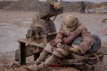 A worker at the Taghabara gold mine rests beside a machine for crushing the ore to powder from which the gold will be recovered.