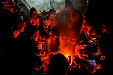 Miners at the Taghabara gold mine warm themselves by a fire at night.