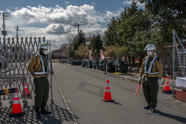 Security staff at the entrance to a restricted area of the town where decontamination work is in progress.   Okuma was totally evacuated in the aftermath of the Fukushima Daiichi nuclear disaster, the...