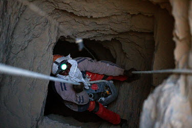 A miner is lowered down a shaft at the Taghabara gold mine.