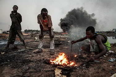 Boys burn cables from computers and other electronic equipment in order to retrieve copper, at Agbogbloshie dump, which has become a dumping ground for computers and electronic waste from all over the...