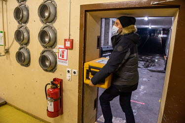 A social worker with a container full of hot meals prepares to go out on outreach in support of homeless people, leaving an underground winter shelter run by the Ville de Genève in an abri PC (a civi...