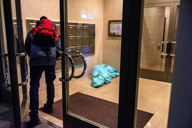 A member of an emergency winter night team, social workers from the Ville de Geneve, on a late night outreach tour in support of homeless people approaches a homeless woman sleeping in the hallway of...