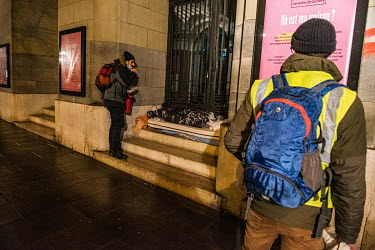 Members of an emergency winter night team, social workers from the Ville de Geneve, on a late night outreach tour in support of homeless people, approaches a homeless person sleeping in a building ent...
