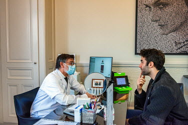 Dr Herve Raspaldo listening to Julien explaining that he would like to have a stronger jaw line, prior to the use of injections of hyaluronic acid fillers at a private clinic in Geneva.