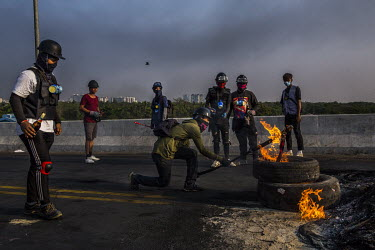 Protestors use molotov cocktails to set the road and tyres on fire in an attempt to block military and police joint security forces.