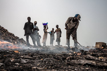 A woman sells packets of water as people burn cables from computers and other electronic equipment to retrieve copper, at Agbogbloshie dump, which has become a dumping ground for computers and electro...