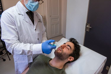 At a private clinic in Geneva, Dr Herve Raspaldo injects his client, Julien, with hyaluronic acid fillers in order to create a stronger jaw line.