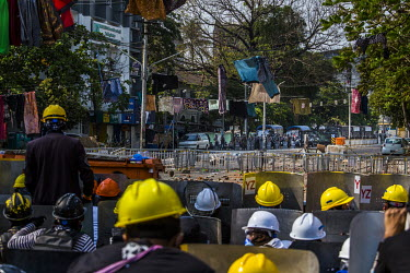 Youth protestors, wearing hard hats and crouched behind homemade shields, prepare to defend themselves against security forces massed at the end of the street. From lines strung across the street acti...