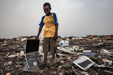 A boy holds an old laptop at Agbogbloshie dump, which has become a dumping ground for computers and electronic waste from all over the developed world. Hundreds of tons of e-waste end up here every mo...