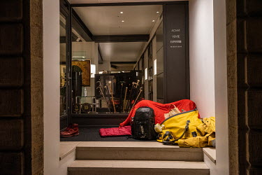 A homeless man sleeping in the doorway to an art gallery in Geneva's historic Old Town.